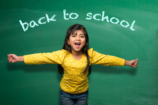"Girl posing in front of chalkboard with words ""back to school"" written across"