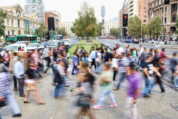 Blurred photo of a crowd of people walking through a city's streets.