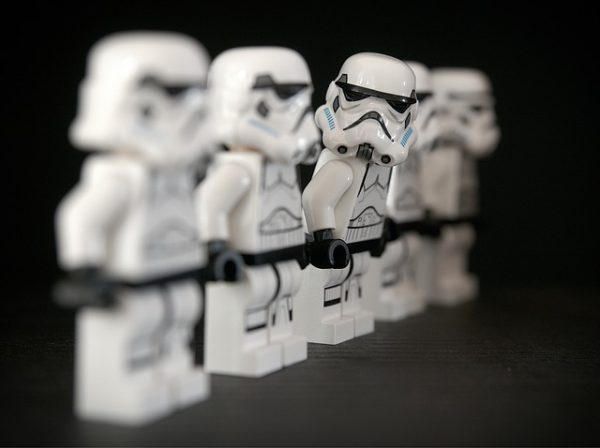 A line of StormTroopers facing forward, while one looks into the camera.